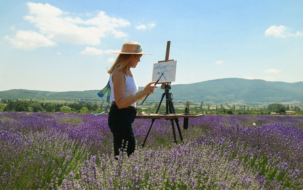 Celeste painting in lavender field. Paintbrush in hand. Provence