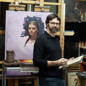 Scott Burdick sketching in studio. behind him is a painting in progress. Supplies out.